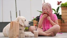 Αγάπη για τα κατοικίδια ζώα - το όμορφο κορίτσι μόδας με τις αφρικανικές πλεξίδες τρώει στην οδό με το σκυλί της απόθεμα βίντεο