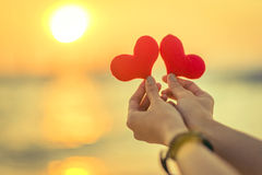 Αγάπη για την ημέρα του βαλεντίνου - δύο κόκκινες καρδιές κρέμασαν στο σχοινί μαζί με το ηλιοβασίλεμα Στοκ εικόνες με δικαίωμα ελεύθερης χρήσης