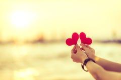 Αγάπη για την ημέρα του βαλεντίνου - δύο κόκκινες καρδιές κρέμασαν στο σχοινί μαζί με το ηλιοβασίλεμα Στοκ φωτογραφίες με δικαίωμα ελεύθερης χρήσης