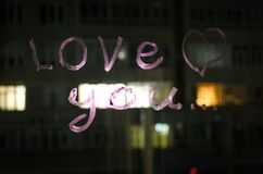 Αγάπη εσείς, κείμενο επιγραφής από το κραγιόν στο γυαλί παραθύρων στη νύχτα άνδρας αγάπης φιλιών έννοιας στη γυναίκα Στοκ Εικόνες