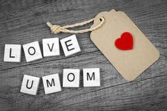 Αγάπη εσείς mom που διατυπώνετε με το κόκκινες σημάδι καρδιών και την ετικέτα εγγράφου Στοκ Φωτογραφίες