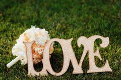 Αγάπη ετικετών στο υπόβαθρο μιας γαμήλιας ανθοδέσμης Στοκ φωτογραφία με δικαίωμα ελεύθερης χρήσης