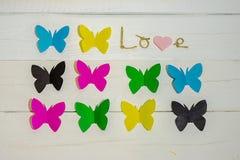 Αγάπη και πεταλούδες επιγραφής στο υπόβαθρο στοκ εικόνες