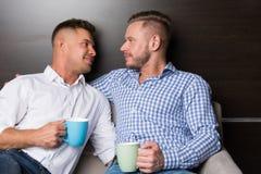 Αγάπη και σχέσεις Δύο ευτυχείς τύποι μαζί στον καναπέ στοκ εικόνες