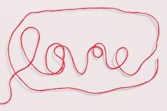 Αγάπη λέξης που γράφεται με το κόκκινο νήμα μαλλιού στο λευκό Στοκ Φωτογραφίες