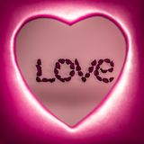 Αγάπη λέξης που σχεδιάζεται με τα τεχνητά λουλούδια μέσα σε μια κόκκινη καρδιά στοκ εικόνα