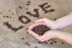 Αγάπη ` λέξης ` φασολιών καφέ και χέρι σε ένα ανοικτό καφέ υπόβαθρο Στοκ εικόνες με δικαίωμα ελεύθερης χρήσης