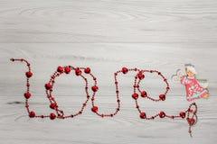 ` Αγάπη ` που γράφει από τις κόκκινες χάντρες Στοκ Φωτογραφίες