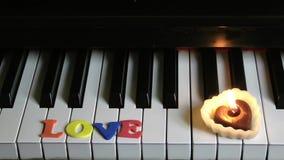Αγάπη στα κλειδιά πιάνων και το φως κεριών απόθεμα βίντεο