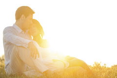 Αγάπη της νέας συνεδρίασης ζευγών στη χλόη στο πάρκο ενάντια στο σαφή ουρανό Στοκ Φωτογραφίες