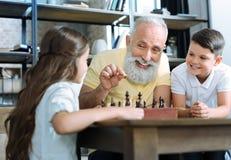 Αγάπη του ανώτερου χαμόγελου κυρίων διδάσκοντας το σκάκι εγγονιών Στοκ εικόνες με δικαίωμα ελεύθερης χρήσης