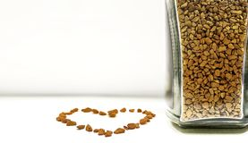 Αγάπη του καφέ - κόκκοι στιγμιαίου καφέ στο μπουκάλι και στο σημάδι καρδιών στοκ εικόνα με δικαίωμα ελεύθερης χρήσης