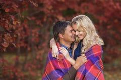 Αγάπη του χαμογελώντας ζεύγους σε ένα πάρκο το φθινόπωρο Στοκ Εικόνες