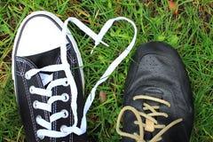 Αγάπη των πάνινων παπουτσιών ζευγών σε ένα υπόβαθρο των δαντελλών χλόης υπό μορφή καρδιάς στοκ φωτογραφίες με δικαίωμα ελεύθερης χρήσης
