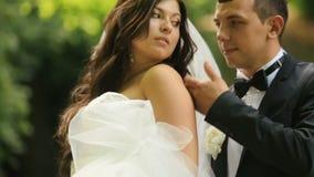 Αγάπη newlyweds - καλλωπίστε το petting ώμο της εξυψωμένης γοητευτικής νύφης του στο ηλιόλουστο θερινό πάρκο Υπαίθριος πυροβολισμ απόθεμα βίντεο