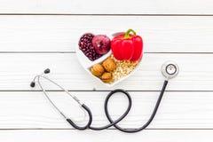Αγαθό προϊόντων για την καρδιά και τα αιμοφόρα αγγεία Τα λαχανικά, φρούτα, καρύδια στην καρδιά που διαμορφώνεται κυλούν κοντά στο Στοκ Φωτογραφίες