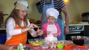 Αγαπώντας γονείς με το χαριτωμένο κορίτσι μικρών παιδιών με το καπέλο αρχιμαγείρων που προετοιμάζει τα μπισκότα στην κουζίνα φιλμ μικρού μήκους