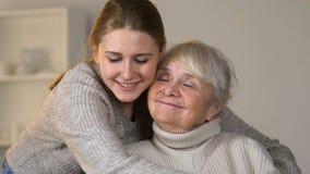 Αγαπώντας εγγονή που αγκαλιάζει την ευτυχή με ειδικές ανάγκες γυναίκα στην αναπηρική καρέκλα, οικογενειακές αξίες φιλμ μικρού μήκους