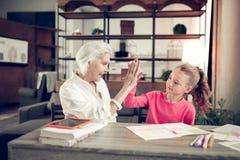 Αγαπώντας εγγονή που δίνει υψηλά πέντε στη δροσερή γιαγιά της στοκ φωτογραφία