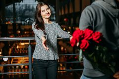 Αγαπώντας ζεύγος, άτομο με την κρύβοντας ανθοδέσμη των τριαντάφυλλων πίσω από την πλάτη του Στοκ Εικόνες