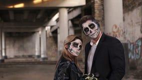 Αγαπώντας ζεύγος αποκριών στα κοστούμια των σκελετών και της σύνθεσης κρανίων ζάχαρης απόθεμα βίντεο