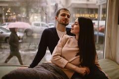 Αγαπώντας ζεύγος Ο τύπος και η φίλη του έντυσαν μέσα στα πουλόβερ και τα τζιν καθμένος ο ένας κοντά στον άλλο στο windowsill μέσα στοκ φωτογραφία με δικαίωμα ελεύθερης χρήσης