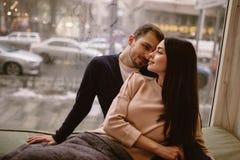 Αγαπώντας ζεύγος Ο τύπος και η φίλη του έντυσαν μέσα στα πουλόβερ και τα τζιν καθμένος ο ένας κοντά στον άλλο στο windowsill μέσα στοκ εικόνες