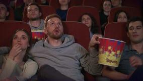 Αγαπώντας ζεύγος που αγκαλιάζει στον κινηματογράφο Οι φίλοι κινηματογράφων απολαμβάνουν την ταινία απόθεμα βίντεο
