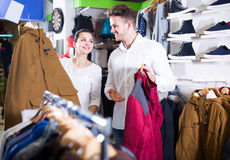 Αγαπώντας ζεύγος που αποφασίζει σχετικά με το θερμό κοστούμι στο αθλητικό κατάστημα Στοκ φωτογραφία με δικαίωμα ελεύθερης χρήσης
