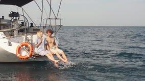 Αγαπώντας ζεύγος που βρίσκεται στο γιοτ εν πλω Διακοπές πολυτέλειας στη βάρκα θάλασσας απόθεμα βίντεο