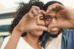 Αγαπώντας ζεύγος που κοιτάζει μέσω της μορφής καρδιών που γίνεται με τα δάχτυλά τους στοκ φωτογραφία με δικαίωμα ελεύθερης χρήσης