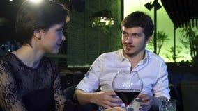 Αγαπώντας ζεύγος που μιλά χαρωπά ενώ κατά μια ημερομηνία στο εστιατόριο απόθεμα βίντεο