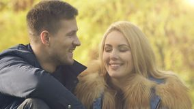 Αγαπώντας ζεύγος που στηρίζεται στο πάρκο φθινοπώρου, που κουβεντιάζει και που αστειεύεται, χρόνος διασκέδασης από κοινού απόθεμα βίντεο