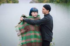 Αγαπώντας ζεύγος που τυλίγεται στη συνεδρίαση καρό στο βουνό υπαίθρια στο ηλιοβασίλεμα Άποψη ποταμών Άνδρας και γυναίκα που ταξιδ Στοκ φωτογραφία με δικαίωμα ελεύθερης χρήσης