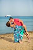 Αγαπώντας ζεύγος που χορεύει και που φιλά στην άμμο στην παραλία θάλασσας στο καλοκαίρι Στοκ εικόνα με δικαίωμα ελεύθερης χρήσης