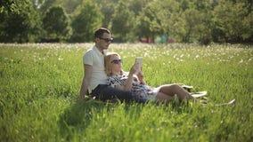 Αγαπώντας ζεύγος στα γυαλιά ηλίου διαβασμένο στο ηλιοβασίλεμα βιβλίο στον τομέα με τις πικραλίδες απόθεμα βίντεο