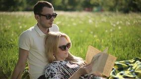 Αγαπώντας ζεύγος στα γυαλιά ηλίου διαβασμένο στο ηλιοβασίλεμα βιβλίο στον τομέα με τις πικραλίδες φιλμ μικρού μήκους