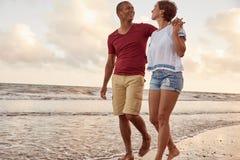 Αγαπώντας ζεύγος στα σπάζοντας κύματα Στοκ Εικόνες