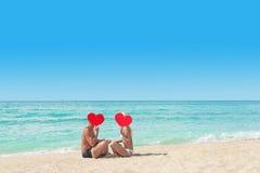 Αγαπώντας ζεύγος στην αμμώδη παραλία θάλασσας με τις κόκκινες καρδιές - βαλεντίνος του ST Στοκ Εικόνες