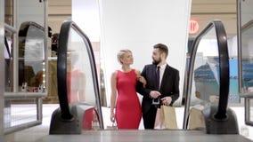 Αγαπώντας ζεύγος στην κυλιόμενη σκάλα στο κατάστημα απόθεμα βίντεο
