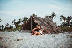 Αγαπώντας ζεύγος στην παραλία κοντά στην καλύβα στοκ εικόνες