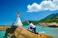 Αγαπώντας ζεύγος στην παραλία θάλασσας - ένα άτομο που κάνει την πρόταση με την ανθοδέσμη Στοκ φωτογραφία με δικαίωμα ελεύθερης χρήσης