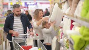 Αγαπώντας θετικοί γονείς και ευτυχές κορίτσι που ψωνίζουν για τα μαξιλάρια δωματίων ύπνου στο κατάστημα του εγχώριου ντεκόρ φιλμ μικρού μήκους