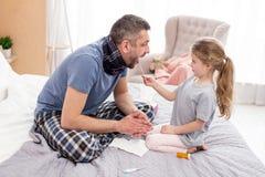 Αγαπώντας κορίτσι που εξετάζει τον άρρωστο μπαμπά της Στοκ Εικόνες
