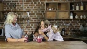 Αγαπώντας κόρη που αγκαλιάζει τη μητέρα στην κουζίνα απόθεμα βίντεο