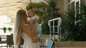 Αγαπώντας μωρό εκμετάλλευσης μητέρων στα όπλα της και το φίλημα τον Στοκ εικόνα με δικαίωμα ελεύθερης χρήσης