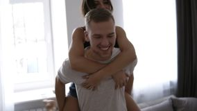 αγαπώντας νεολαίες ζευγών Γυναίκα Brunette στα εσωτερικά ενδύματα που αγκαλιάζει τον άνδρα από την πλάτη του που χαλαρώνει απολαμ απόθεμα βίντεο