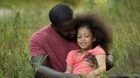 Αγαπώντας πατέρας που αγκαλιάζει tenderly τη μικροσκοπική κόρη του, που ξοδεύει το χρόνο μαζί υπαίθριο στοκ φωτογραφίες με δικαίωμα ελεύθερης χρήσης