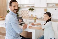 Αγαπώντας πατέρας που βοηθά την κόρη του για να κάνει την εργασία Στοκ Εικόνα