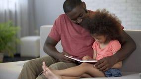 Αγαπώντας πατέρας που διδάσκει τη μικρή σγουρός-μαλλιαρή κόρη του πώς να διαβάσει, προσοχή στοκ εικόνες με δικαίωμα ελεύθερης χρήσης
